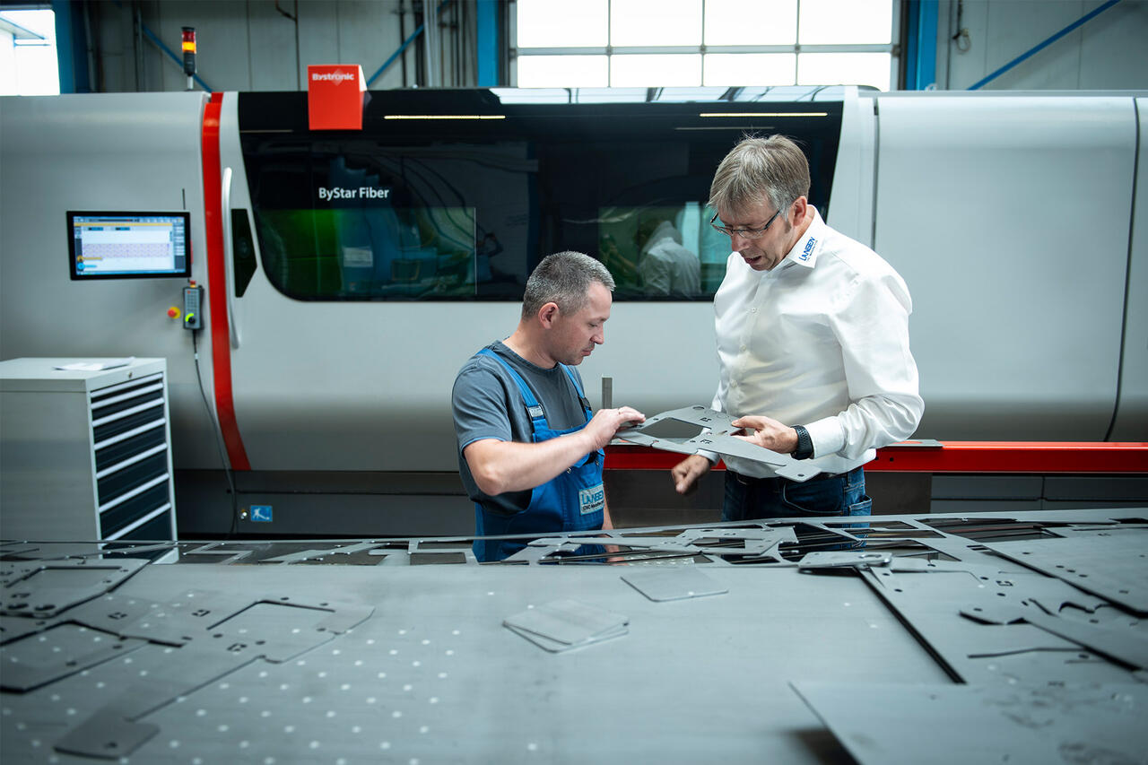 Franz Langen (on the right) in conversation with the operator of the ByStar Fiber 8025. The quality of the cutting edges is essential for the further processing of the parts. A high-quality laser cut eliminates the need for costly reworking.