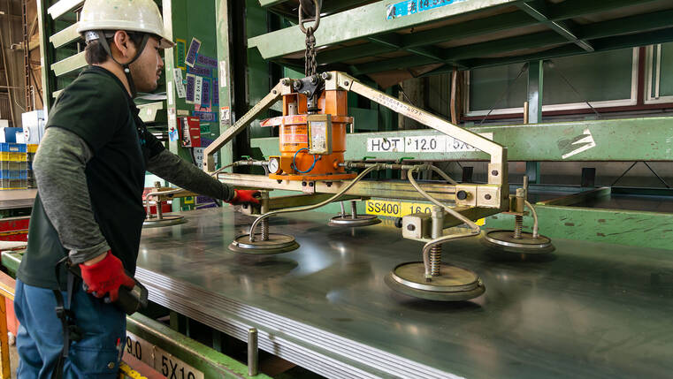 Large metal sheets are lifted onto the cutting machines using suction cups
